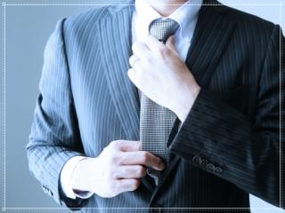 スーツ姿でネクタイを締める男性画像
